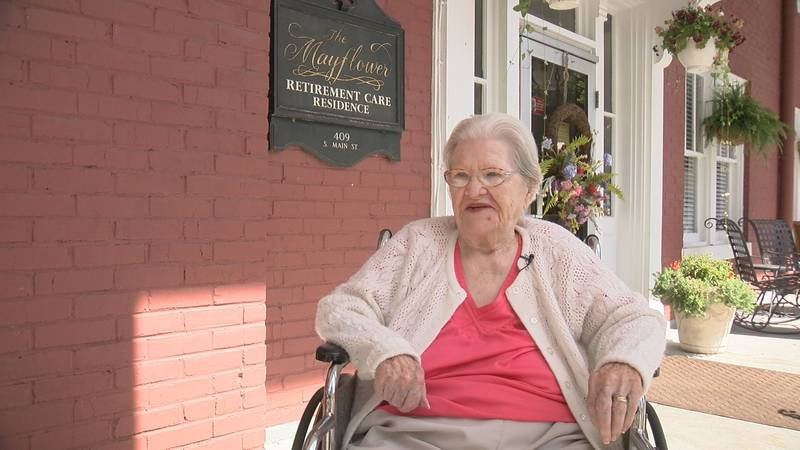 Centenarian Anne Durr sits on the front porch of the Mayflower assisted living residence.