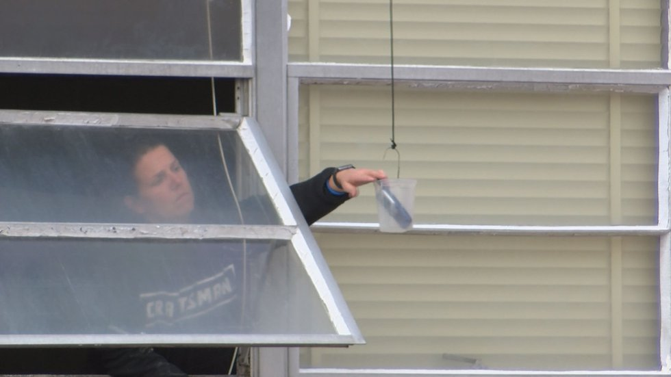 Mock Hostage reaches for a phone, delivered by a drone during a training drill.