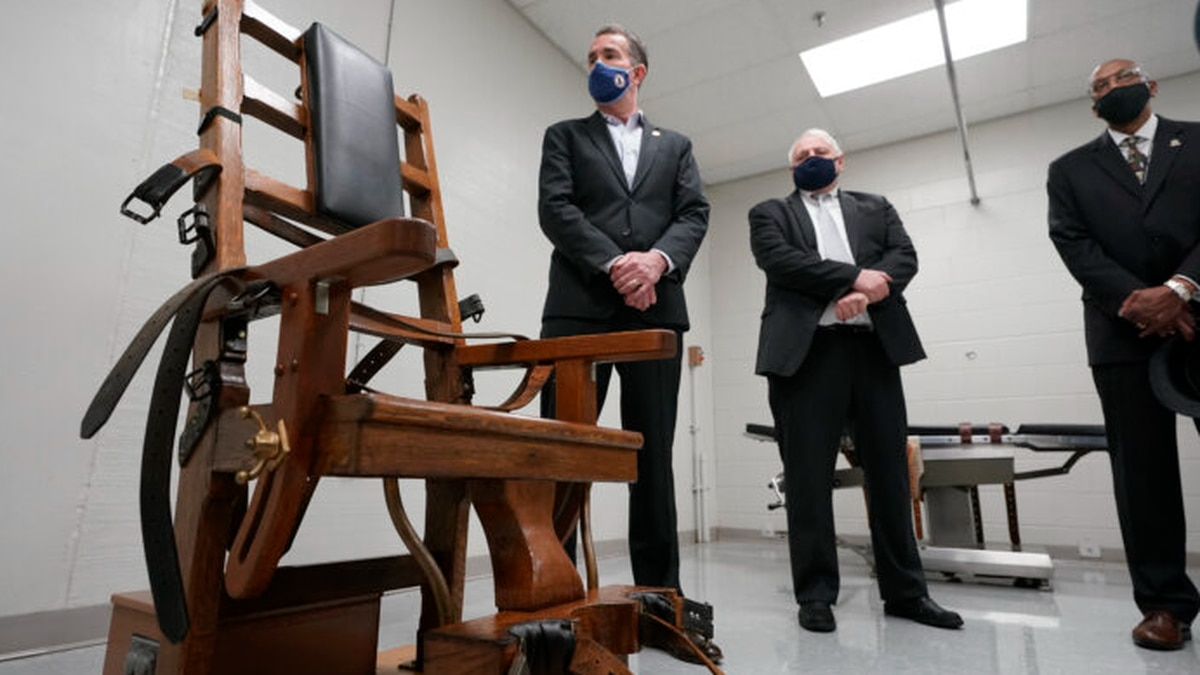 Virginia Gov. Ralph Northam, left, looks over the electric chair in the death chamber at...
