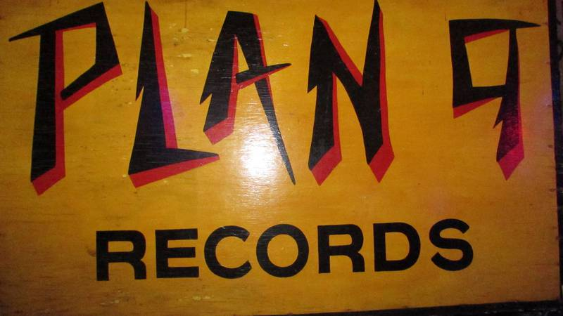 A Plan 9 Records sign, formerly hung above the store's second location, sits on a stool. The...