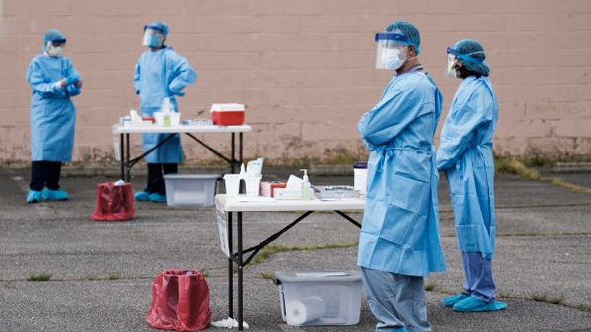 Volunteers wait for patients at a walk-up COVID-19 testing site set up by the health department...