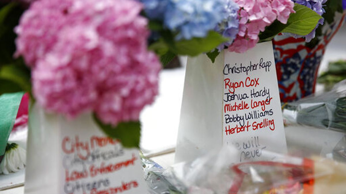 Victims' names cover part of a flower vase at a makeshift memorial for victims of a mass...