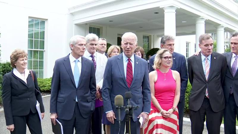 President Joe Biden stands with a bipartisan group of senators in front of the White House on...