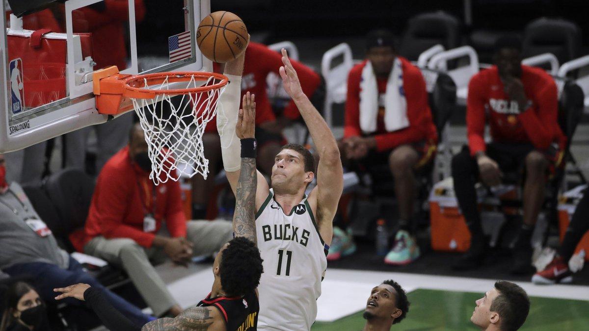 Milwaukee Bucks' Brook Lopez (11) shoots against Atlanta Hawks' John Collins (20) during the...