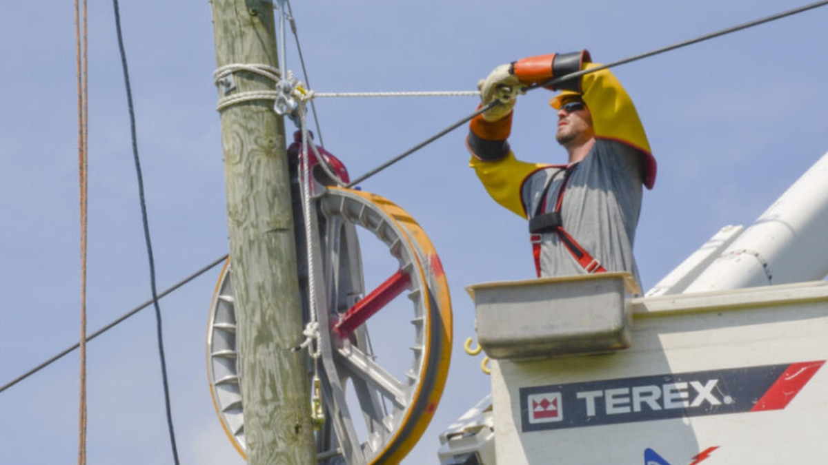 A Rappahannock Electric Cooperative employee strings fiber optic cable.