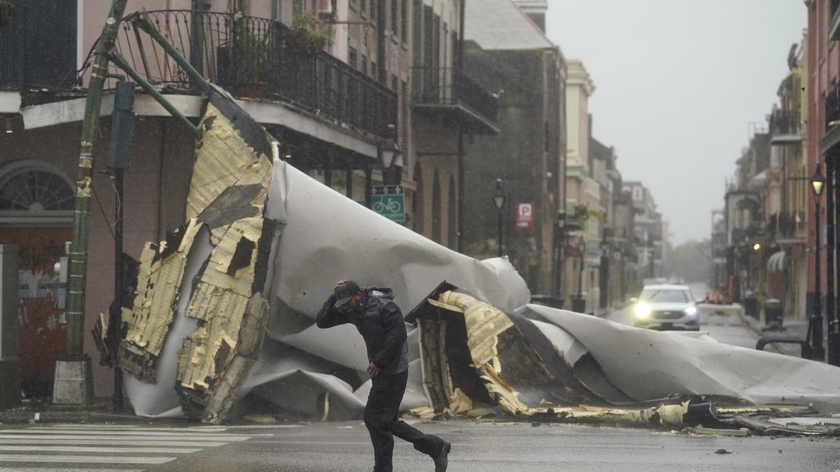 A man passes by a section of roof that was blown off of a building in the French Quarter by...