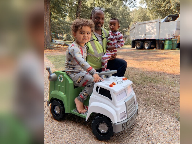Darrel McNeil sits next to Bodhi, Carden and their new mini version of McNeil's garbage truck.