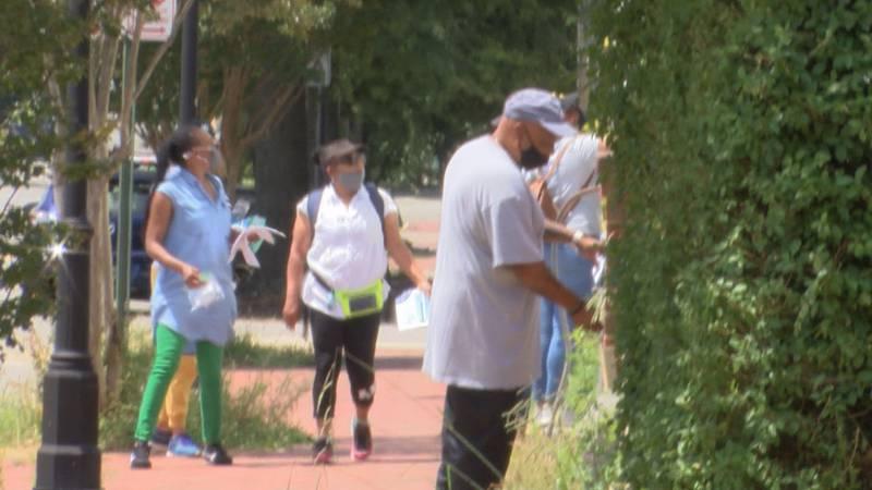 Volunteer canvassers go door-to-door to notify people of mobile vaccine van on N 25th Street.