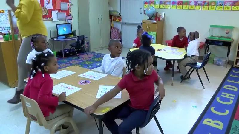 Students in an early childhood program sit at tables.