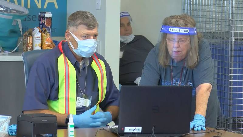 Poll workers wearing protective gear while registering hundreds of voters casting ballots in...