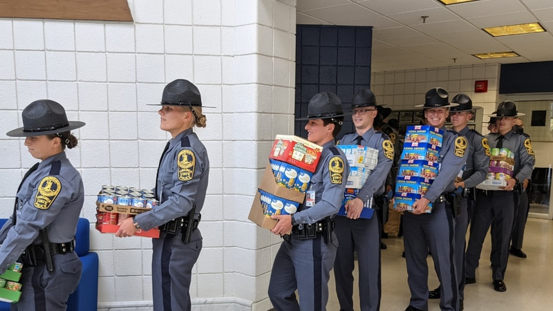 Virginia State Police trooper trainees carrying non-perishable items.