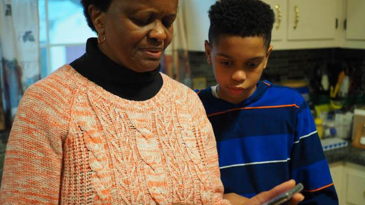 Thirteen-year-old Isaiah helps his grandmother, Carolyn Richardson, find a picture on her...
