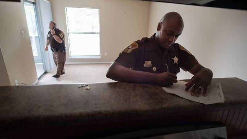 Deputies from the Henrico County Sheriff's Department process an eviction on July 12, 2018. The...