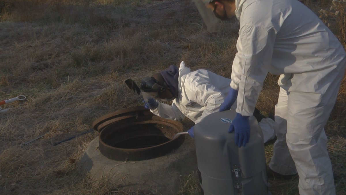 Facilities management workers place waste water testing technology in a manhole.