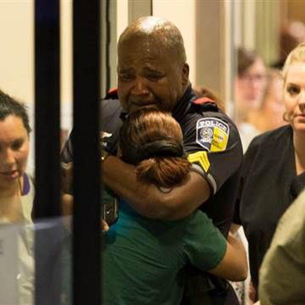 A DART (Dallas Area Rapid Transit) police officer receives comfort at Baylor University...