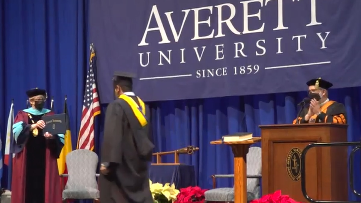 An Averett University graduate walks across the stage during an intimate graduation ceremony on...