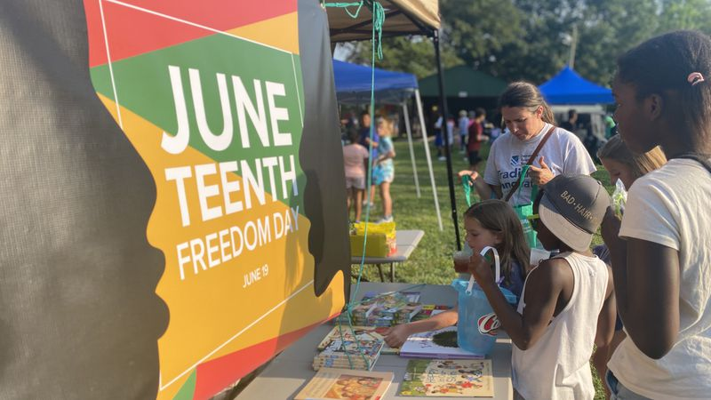 FILE: Children choose books from a table at a Juneteenth event.