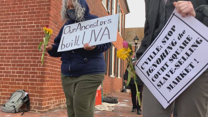 Community members place flowers on ground of former Charlottesville slave auction block, while...