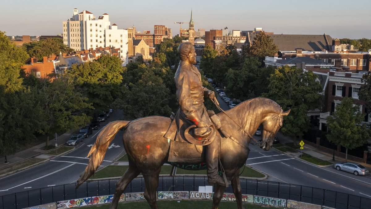 The statue of Confederate General Robert E. Lee is bathed in the late sun on Monument Avenue in...