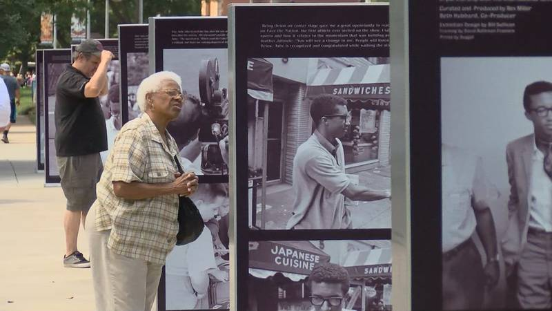 Visitors look at a photo exhibit in honor of Arthur Ashe.
