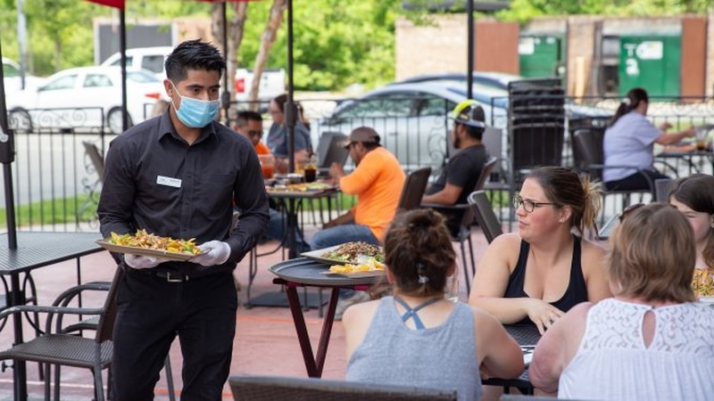 A server brings food to customers on the patio at Plaza Azteca in Henrico, Va., May 16, 2020.