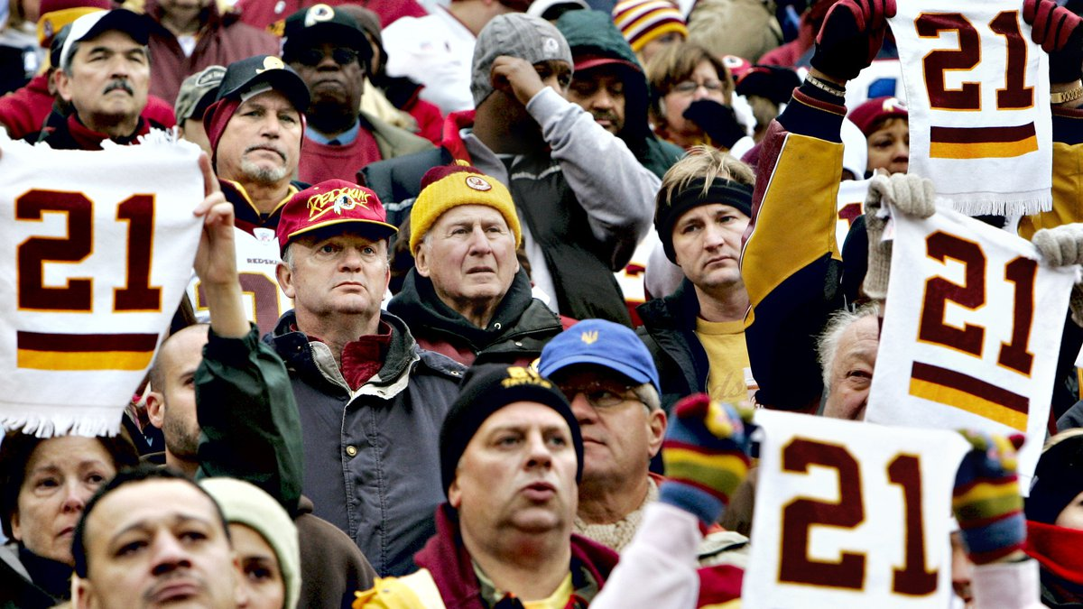 FILE - In this Dec. 2, 2007, file photo, solemn football fans hold up towels with No. 21 in...