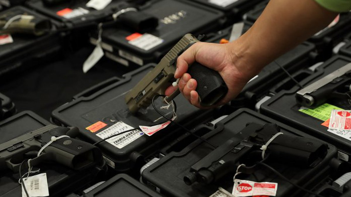 A potential buyer tries out a gun which is displayed on an exhibitor's table during the...