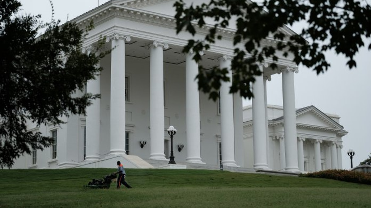 A state prison inmate mows grass on Capitol Square.