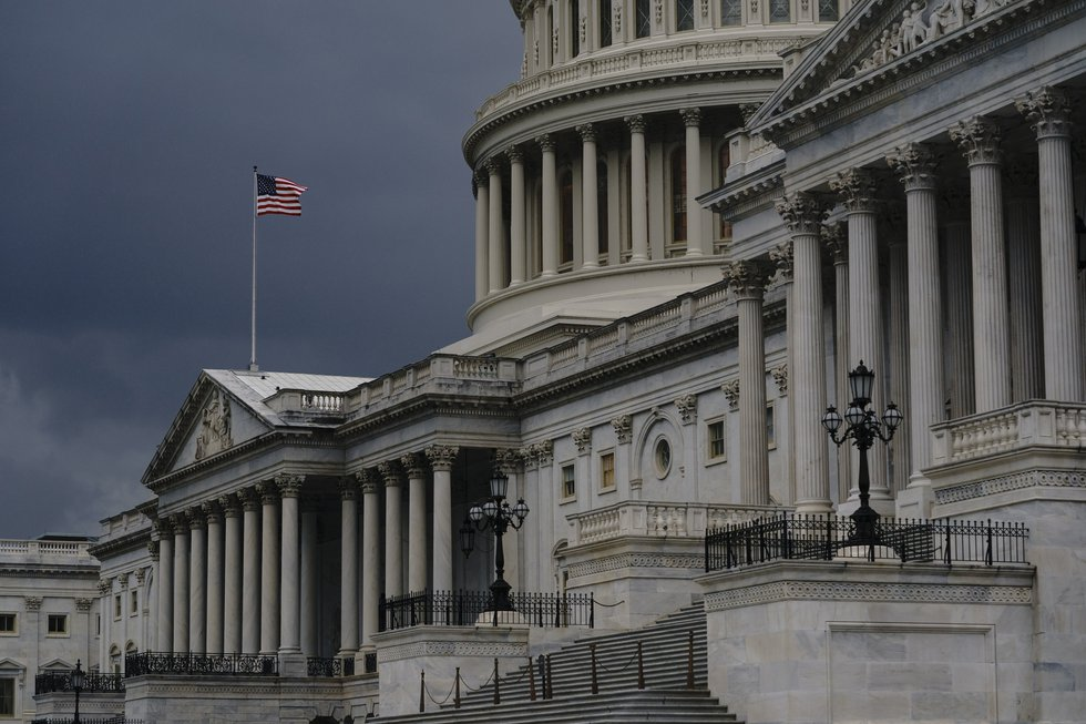 FILE - In this Aug. 3, 2020, file photo dark clouds and heavy rain sweep over the U.S. Capitol...