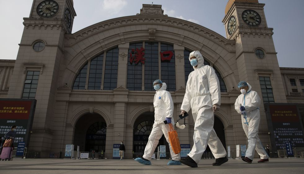 FILE - In this April 7, 2020 file photo, workers in protective overalls walk past the Hankou...