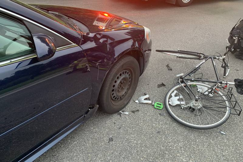 A bike lays on the road next to a damaged car after an accident on Commonwealth Center Parkway.