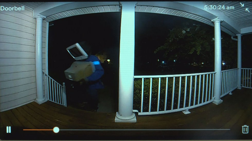 Still from footage from Adrian Garner's home security camera shows a person leaving the TV on...
