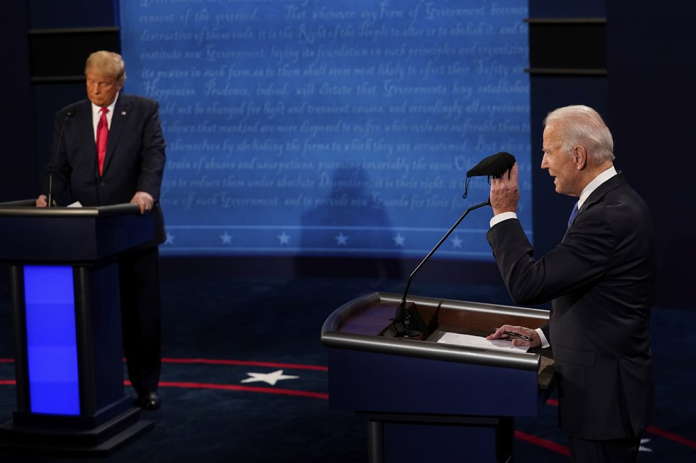 Democratic presidential candidate former Vice President Joe Biden holds up a mask as President...