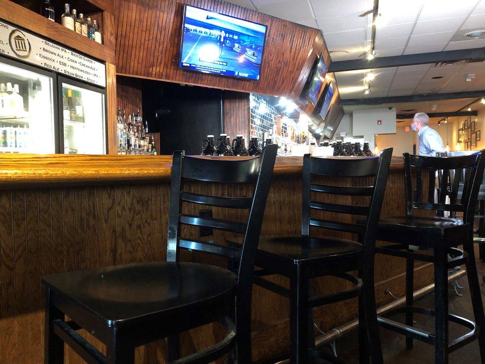 Staff set up bar seating after Governor Northam eases restrictions.