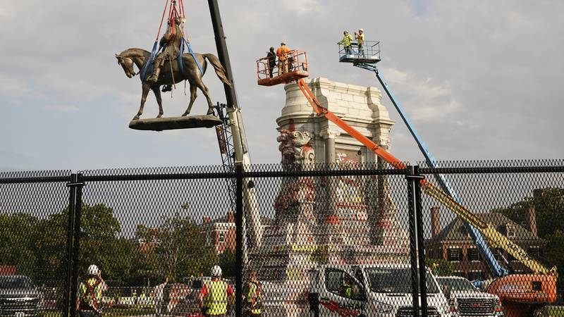Crews remove one of the country's largest remaining monuments to the Confederacy, a towering...