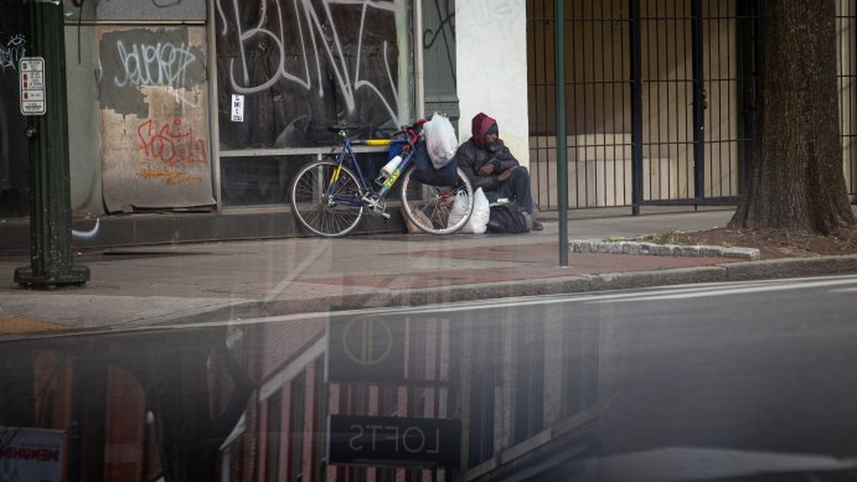 A homeless man sits on Broad Street in Richmond, Va., March 18, 2020.