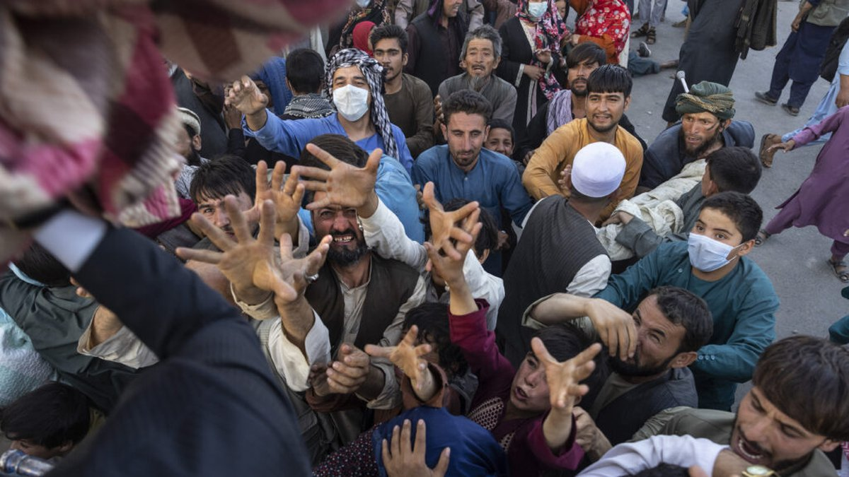 KABUL, AFGHANISTAN - AUGUST 10 : Displaced Afghans reach out for aid from a local Muslim...