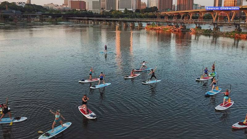 A group practices stand up paddleboard yoga on the James with Waterfront RVA.