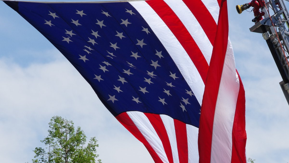 An American flag blows in the wind during services for fallen Watauga County deputies