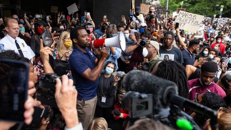 Richmond Mayor Levar Stoney and Police Chief Will Smith (left) speak to a large crowd from the...