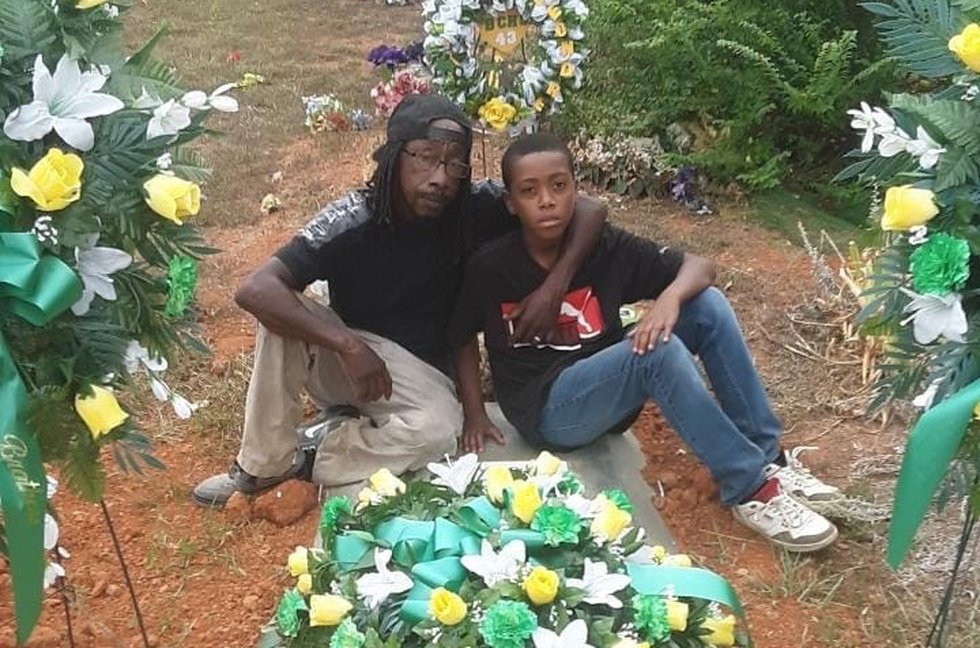 Earl Booker, with 10-year-old son Nayquaris, pictured at the funeral of his son, 16-year-old...