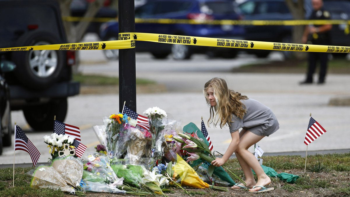 A girl leaves flowers at a makeshift memorial at the edge of a police cordon in front of a...
