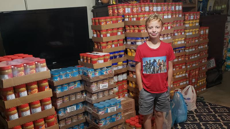 Gavin Price stands in front of the donations of peanut butter jars that have been shipped in...