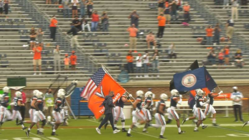 The Virginia football team runs on the field in front of family-only in its season opener at...