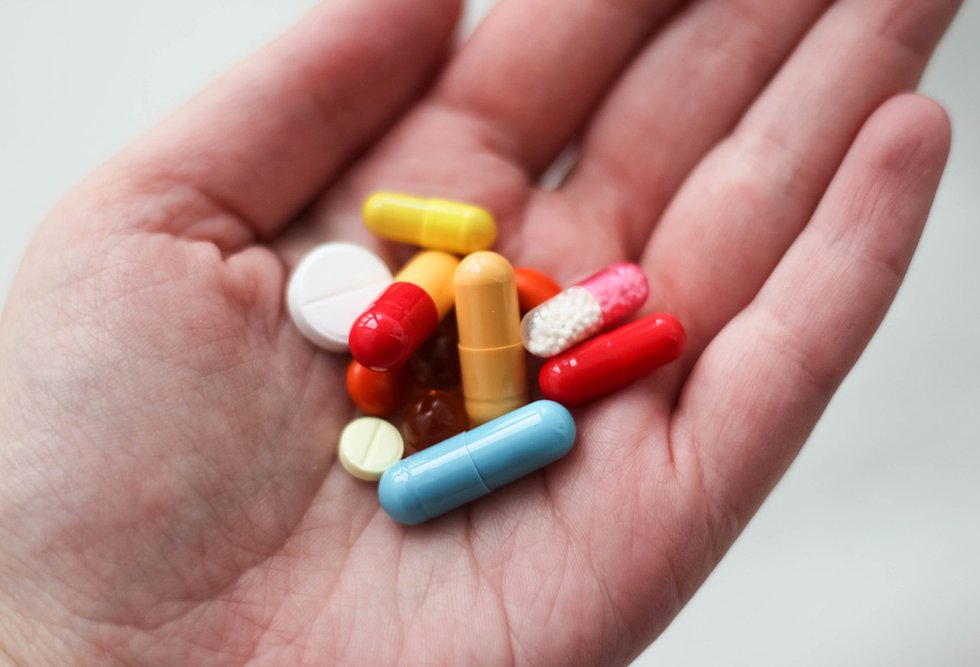 A person holds a variety of pills in the palm of their hand.