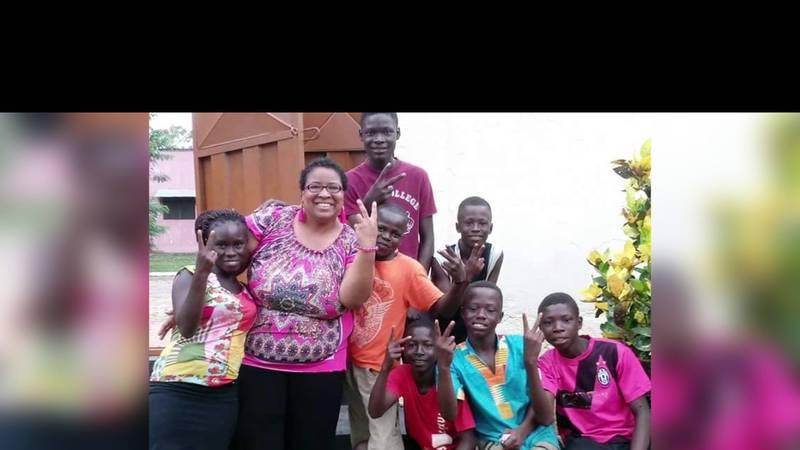 Myra Anderson poses with children in Winneba, Ghana, where she'll be teaching a poetry workshop.