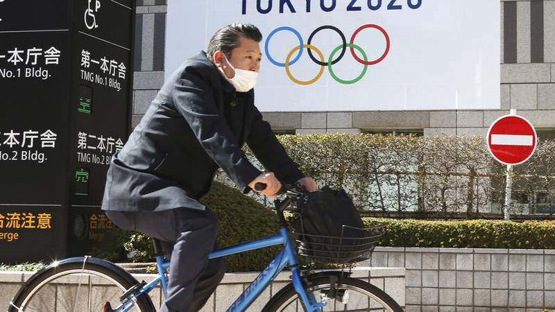 A man wearing a face mask cycles past the logo of the Tokyo Olympics, in Tokyo, Wednesday, Feb....