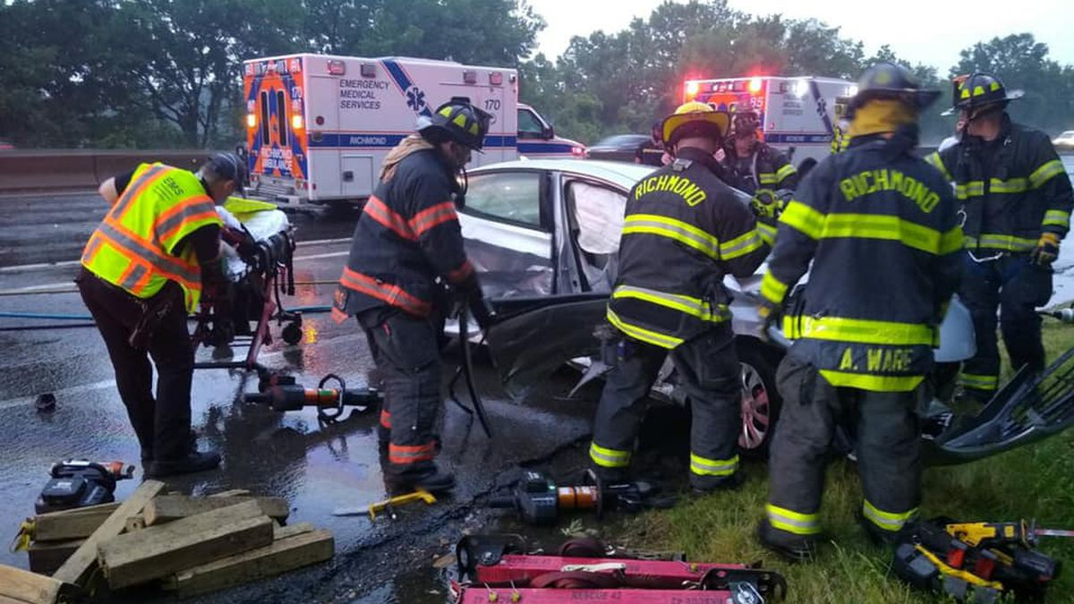 Members of the Richmond Fire Department assist a trapped driver as lanes are blocked on...