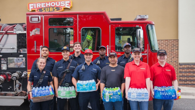 First responders and Firehouse Sub employees holding donated water cases.