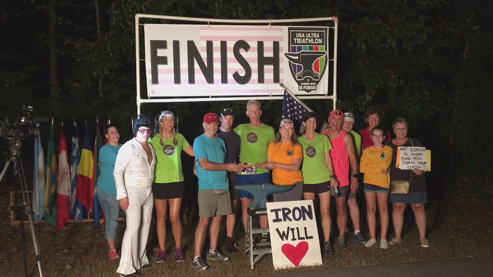 Turner celebrating 45th Ironman race surrounded by support group.